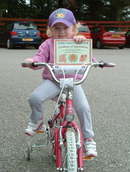 Lena Forysth on her bike and with cycle-ride certificate