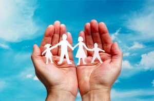 Hands holding paper cut-outs in the shape of a family